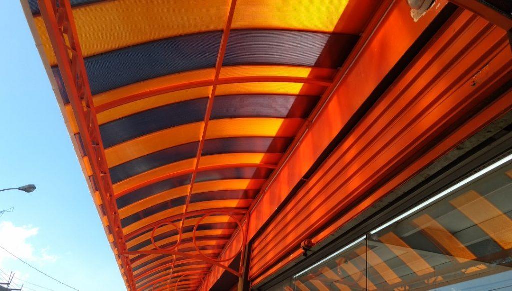 Toldo de porta  curvo Policarbonato Alveolar click cor laranja e fumê - Polysolution