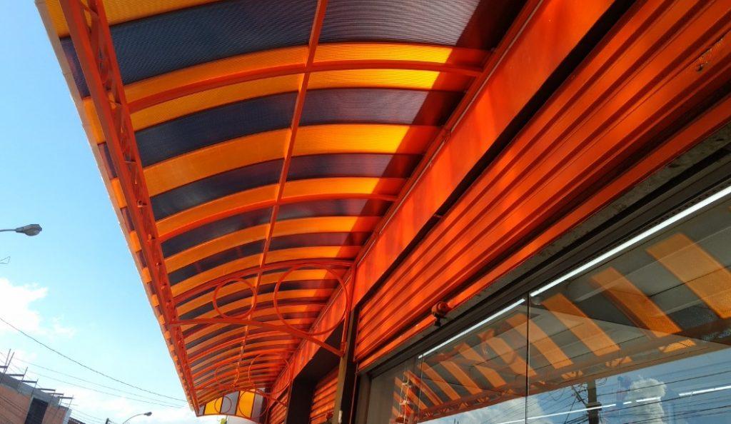 Toldo com as telhas de Policarbonato Alveolar click cor laranja e fumê - Polysolution
