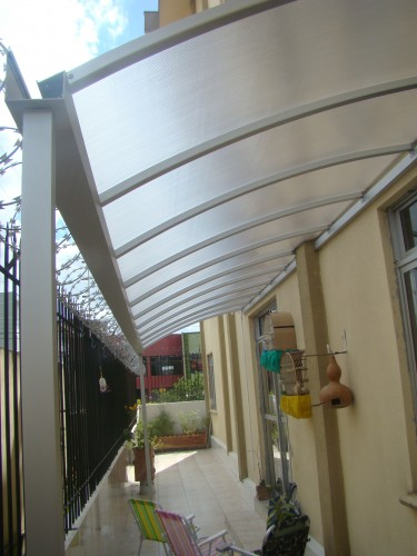 Cobertura de Policarbonato em lateral de predio e muro, inclinada curva, sistema modular CLICK POlysolution, encaixe e monte - Perfil viga-calha PC 4412 + Perfil estrutural aluminio PC 5512